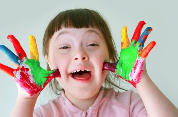 Vesela deklica z Downovim sindromom kaže dlani, pisani od barv.